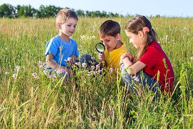 3 enfans observent la nature avec une loupe.L'école Montessori Bilingue Smiles'n Kids située dans le 92 à Issy-les-Moulineaux proche de Meudon applique la pédagogie Montessori et promeut la découverte de la nature via des ateliers jardinage.