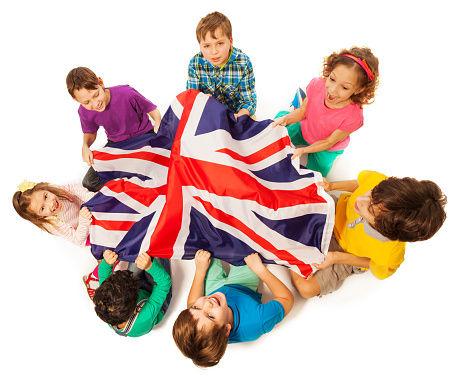 Enfants entourant le drapeau britannique. L'école Montessori Bilingue Smiles'n Kids située dans le 92 à Issy-les-Moulineaux proche de Meudon applique la pédagogie Montessori dans un environnement bilingue anglais-français.