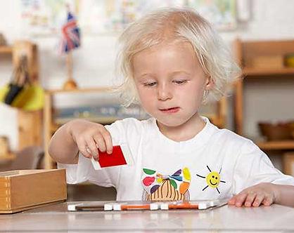 Fillette travaillant avec le matériel Montessori, la 2ème boîte de couleurs. L'école Montessori Bilingue Smiles'n Kids située dans le 92 à Issy-les-Moulineaux proche de Meudon applique la pédagogie Montessori.