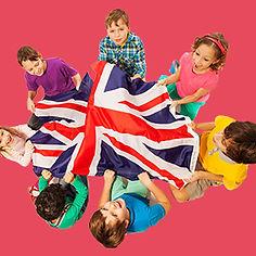 Enfants entourant le drapeau britannique, contens d'apprendre l'anglais.