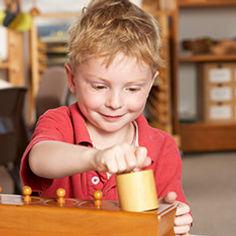 Enfant au travail avec matériel Montessori dans une école Montessori : les blocs de cylindres