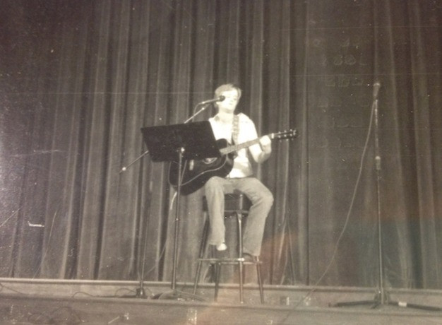 Author as a 17 year old on stage with a guitar. Black and white photo.
