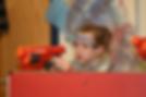Little girl crouching behind cover during a Nerf gun war