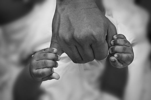 Hands of son holding his father's finger