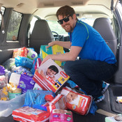 Youth in Need volunteer unloads donations