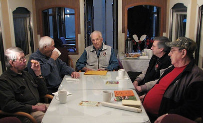 A group of volunteers gather around a table to share their stories