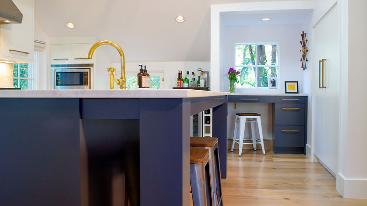 Kitchen with navy blue cabinetry, white countertops, and golden fixtures.