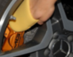 Close-up of rim and caliper brake units with sponge-covered hand applying ceramic coating