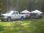 White Four Door pickup with equipment trailer and two white topped tents housing two priuses