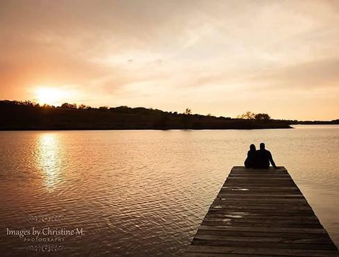 Engaged couple on lake dock  at sunset