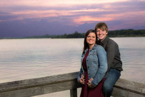 Engaged couple at lake at sunset