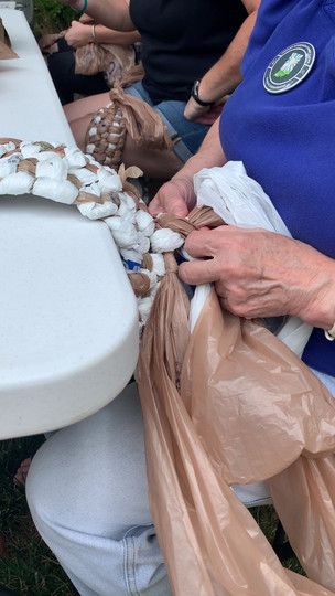 An attendee at the Craft for Climate event weaves bags together.