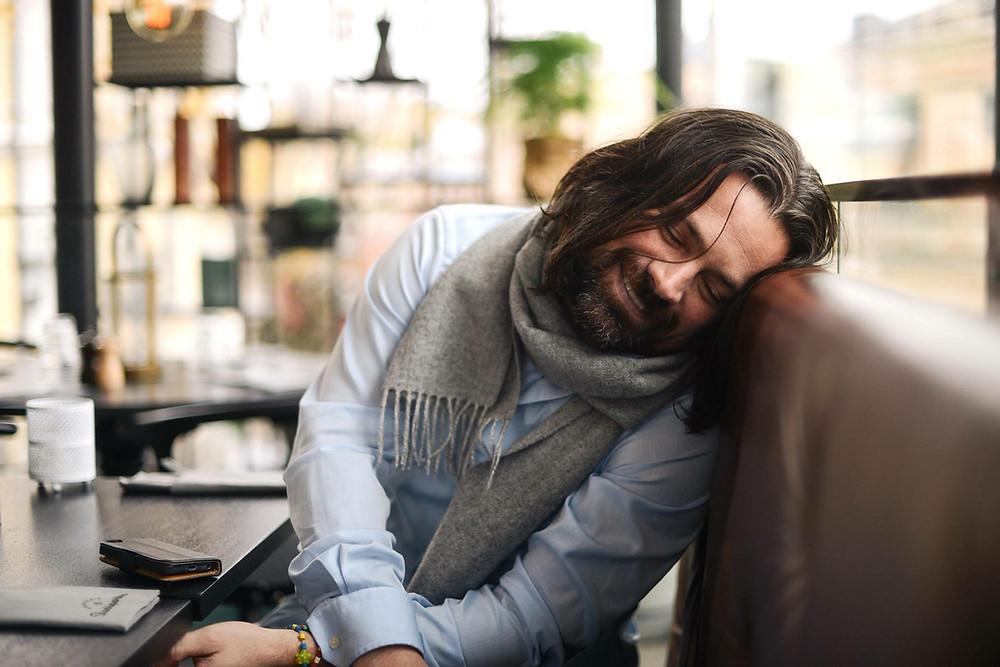 Långhårig man sittandes i en soffa. Blå skjorta och halsduk.