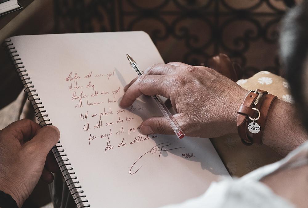 Ett skrivblock med en dikt skriven av samma hand som håller i blocket.