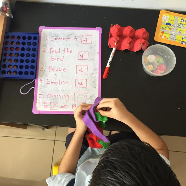 One of our kids working on independently completing multiple tasks.