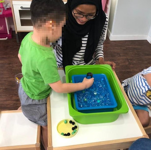 Akmal beams with pride as her kids at Play Group practice fine motor skills by using tongs to pick up marbles. Fine motor activities in the early years help children refine their pincer grasp as well as their handwriting skills in the later stage.