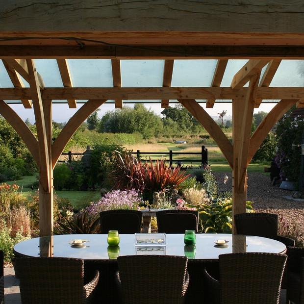 Outdoor dining under oak frame loggia