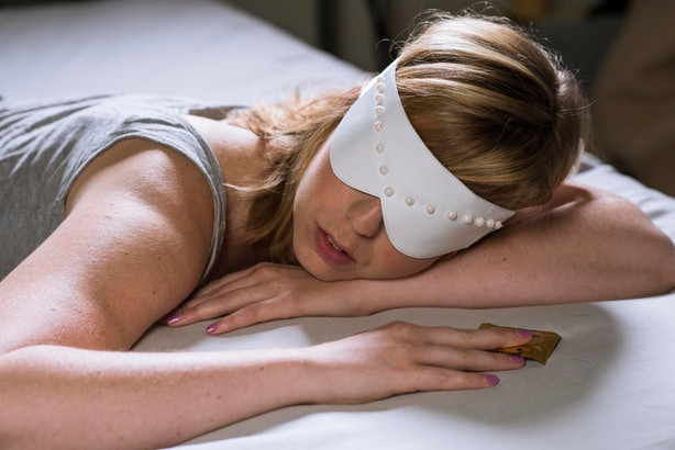 Woman in bed with white beaded sleep mask