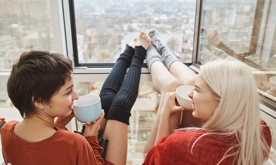 Two friends sitting near a window