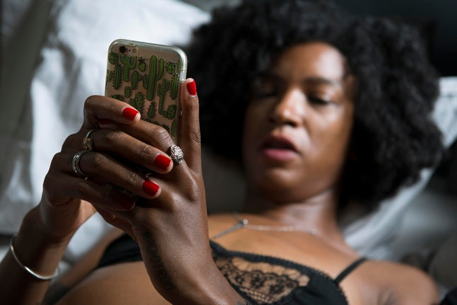 Black woman lying in bed with mobile phone