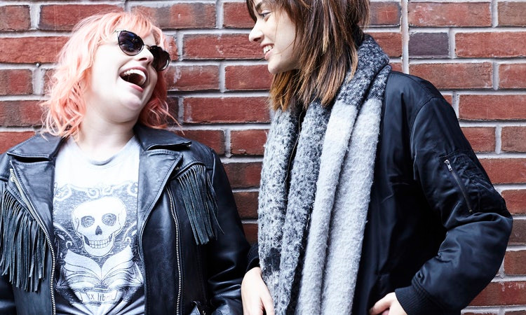 Two women in leather jackets laughing