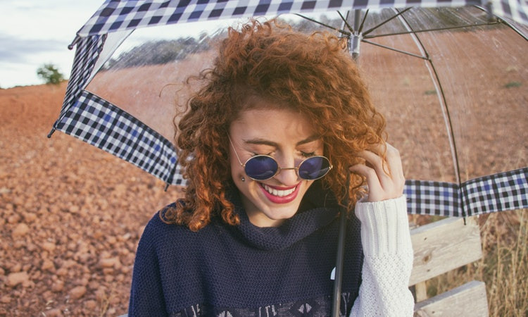 Red haired woman with umbrella smiling