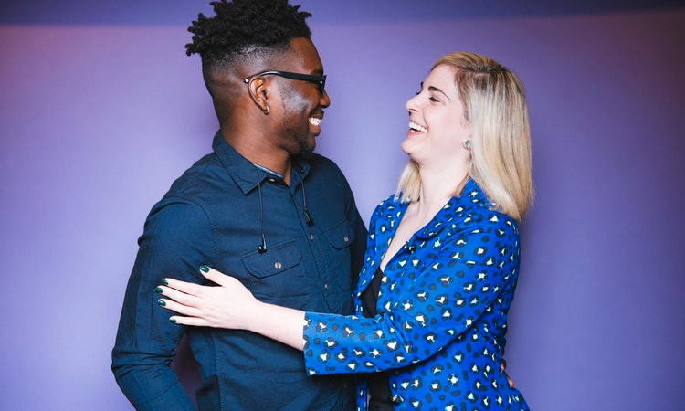 Black man, white woman laughing together.