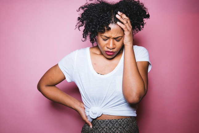 Black woman headache pink background