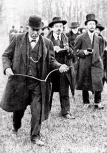 A gentleman using a dowsing stick to find water. Circa 1870.