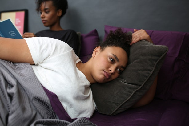 Two black women in bed. One reading. One back turned looking sad.