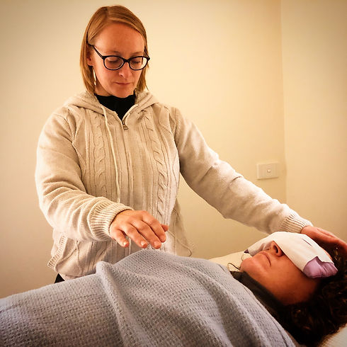 Woman lying down with eyemask covering her eyes, another woman has her hands hovering over her chest and head as she performs Reiki on her client