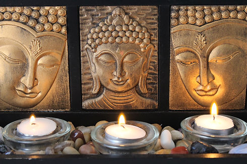 Three candles in a row sitting in a bed of gemstones, gold buddhist art in the background
