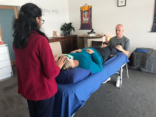 Woman lying on a massage table, a lady has her hands on her head, a man has his hands on her feet
