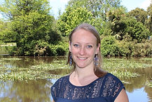 Lady in a blue top standing in front of a lake and trees