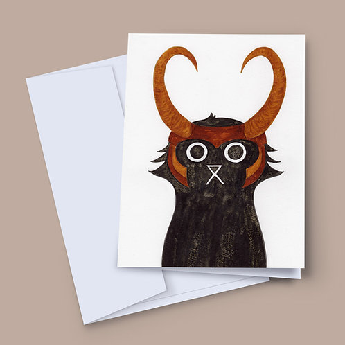 A 7x5 inch greeting card featuring an ink and salt black cat illustration wearing Loki's helmet