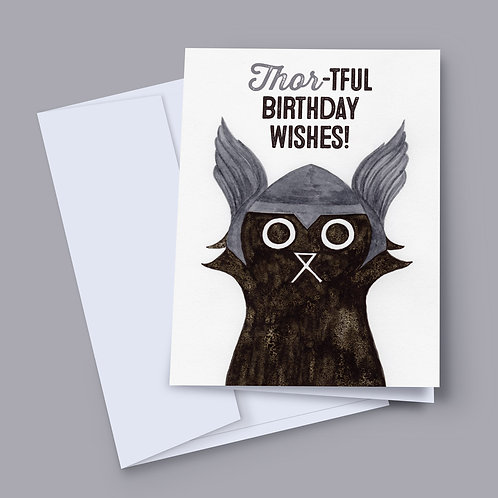 A 7x5 inch birthday card featuring an ink and salt black cat illustration wearing Thor's helmet