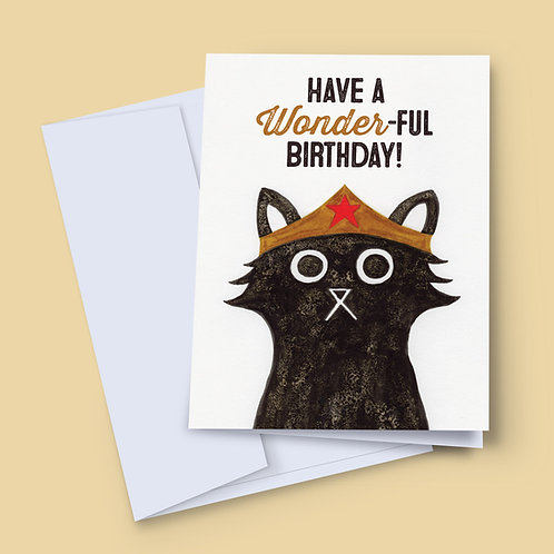 A 7x5 inch birthday card featuring an ink and salt black cat illustration wearing Wonder Woman's head dress
