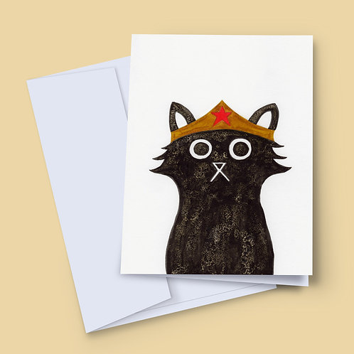 A 7x5 inch greeting card featuring an ink and salt black cat illustration wearing Wonder Woman's head dress