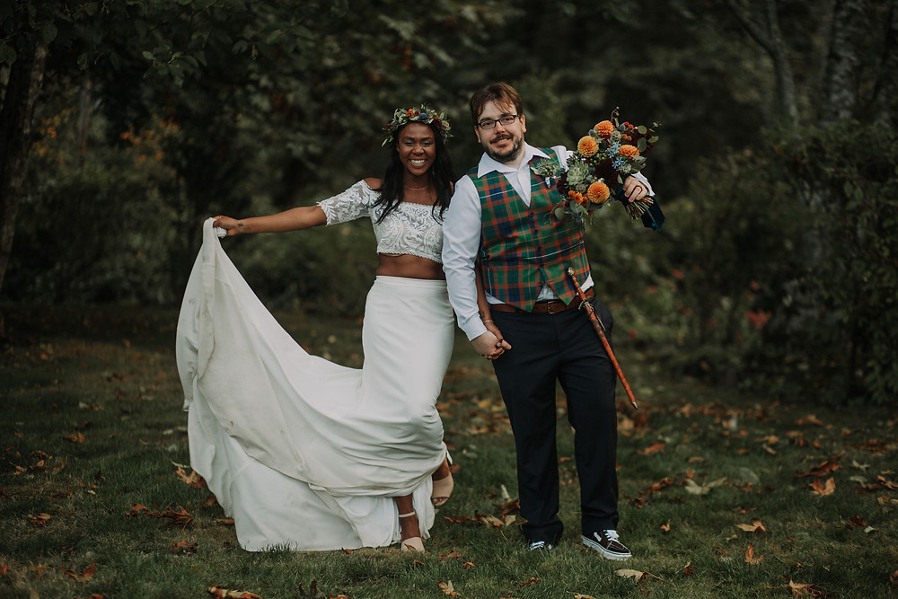Bride with Flower Crown and Groom Holding Bride's Bouquet Pose in the Forested Venue of their Seattle Wedding