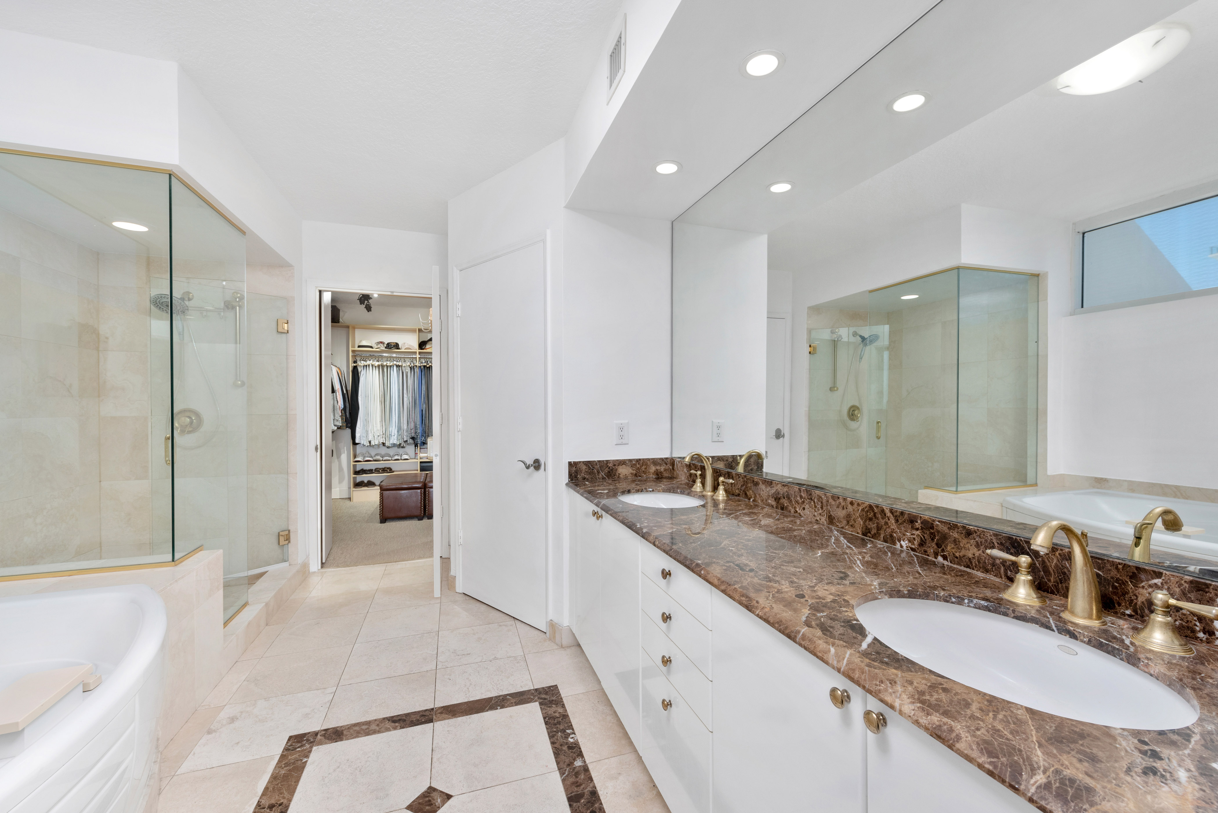 Master bathroom with entrance to large walk-in closet