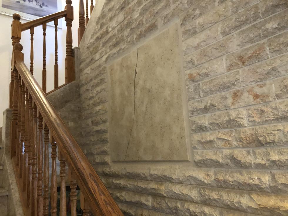 """Stone """"Memory of Temple"""" artwork in stairway"""
