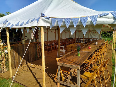 Our Rustic Marquee showing our Wooden Trestle tables and chairs and Mobile bar
