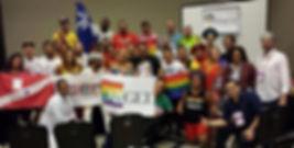 Imagem de representantes de organzações afiliadas a ABGLT abraçados e segurando bandeira da ABGLT.