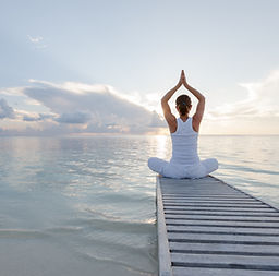 Caucasian woman practicing yoga at seash
