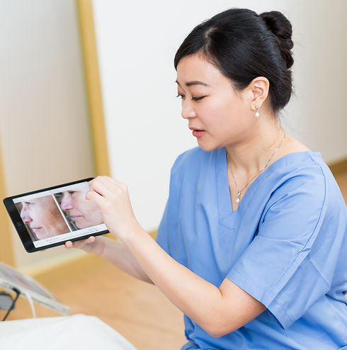 Doctor in blue scrubs pointing to iPad