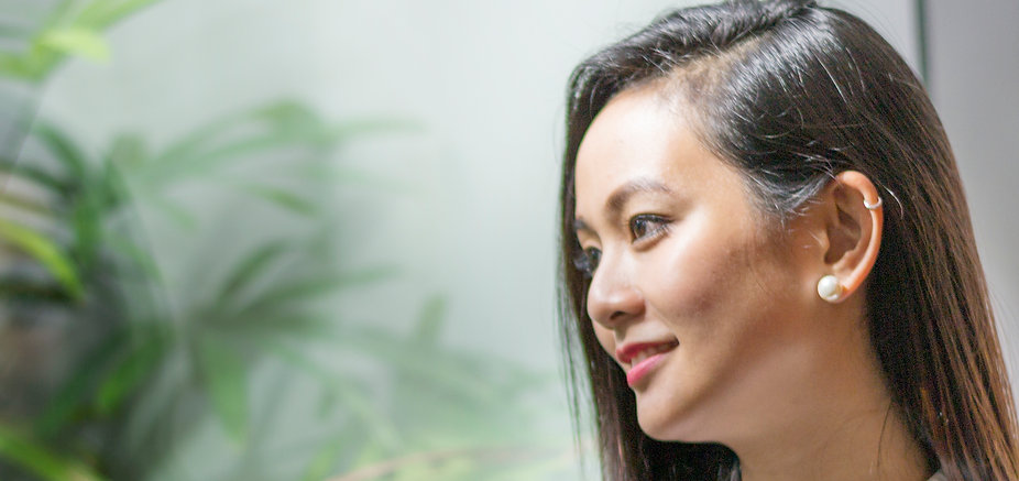 Side profile of woman smiling against green background