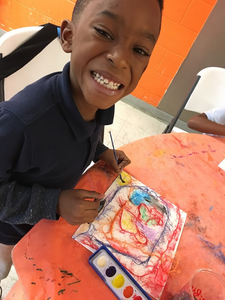 Child Smiling while creating a painting