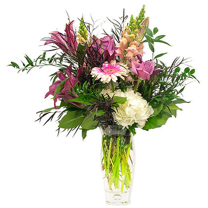 Natural woodsy and freshly gathered. Lush white hydrangea pink hybrid lilies snapdragons gerber daisies and lavender roses