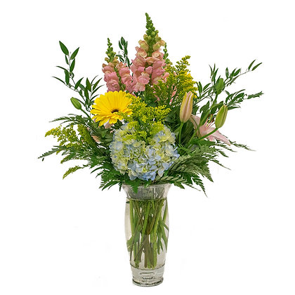Pink asiatic lilies and snapdragons blue hydrangea and yellow gerber daisies with solidago fern and ruscus in a regal crystal