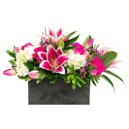 White Hydrangea pink Hybrid Lilies pink Roses pink Tulips and pink Waxflower with Italian ruscus and pittosporum